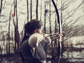 foto of bow arrow  - Medieval archer woman she wearing a chainmail and use a bow and arrow gloomy forest cross - JPG