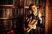 picture of school carnival  - A boy stands in the library by the bookshelves with many old books and holds old manuscripts - JPG