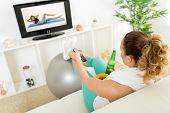 stock photo of exercise  - Lazy woman in sport clothing sitting front of the TV and doesn - JPG