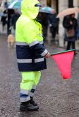stock photo of policeman  - policeman in uniform with the red flag to signal the roadblock - JPG