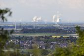 stock photo of long distance  - Long distance view over rural landscape to steaming coal-fired power stations framed by branches and leafs of some trees.