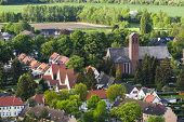 foto of west village  - High angle view of a little west German village with a church surrounded by trees near Aachen - JPG