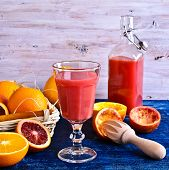 pic of orange-juice  - The juice of red and orange oranges in a glass beaker surrounded by whole and cut fruits in rustic style - JPG