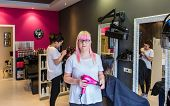 stock photo of beauty parlor  - Portrait of woman hairdresser with a hairdryer in her hand standing in a hair and beauty salon with customers in the background - JPG