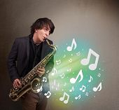 stock photo of saxophone player  - Attractive young musician playing on saxophone while musical notes exploding - JPG