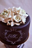 foto of sugar paste  - Gorgeous birthday cake covered with black fondant and decorated with white sugar paste flowers - JPG