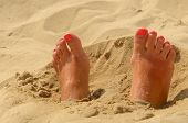 picture of painted toenails  - Woman feet on the sand with manicure - JPG