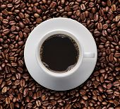 stock photo of coffee crop  - Bird eyes view of coffee cup on raw coffee beans - JPG