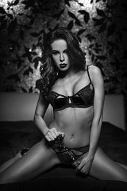 image of handcuff  - Sexy woman kneeling on bed with handcuffs in hotel room black and white - JPG