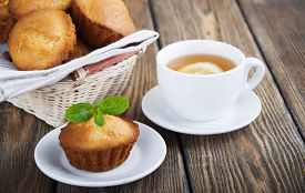stock photo of bakeshop  - Homemade muffins and a cup of tea with lemon on wooden background - JPG