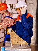 stock photo of millwright  - Group people  builder and old man with circular saw - JPG