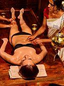 stock photo of panchakarma  - Young woman full lenght having stomach Ayurveda spa treatment - JPG
