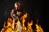 picture of woman dragon  - pensive woman with a dragon egg in the fire isolated on black - JPG