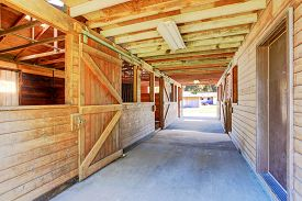 stock photo of stall  - Large and authentic horse barn with many stalls - JPG