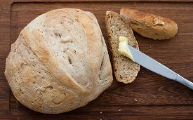 image of home-made bread  - knife home made bread and butter on wooden board  - JPG