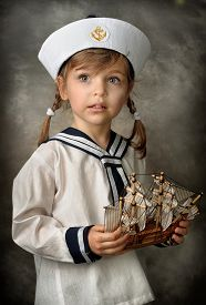 image of little girls photo-models  - Little girl dressed as a sailor holding a wooden ship with white sails - JPG