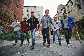 picture of hooligan  - Group of spiteful hooligans walking along grunge brick houses - JPG