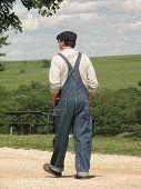 picture of tallgrass  - Picture of a farmer in overalls taking a stroll at the Tallgrass prairie National Preserve in Chase County Kansas - JPG