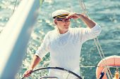 sailing, age, tourism, travel and people concept - happy senior man in captain hat on steering wheel poster