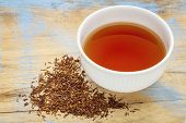 rooibos red tea  -  a white cup of a hot drink and loose leaves on grunge wood background, tea made  poster