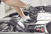 Cropped image of automobile mechanic repairing car in automobile store poster