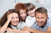pic of happy family  - Happy family of 4 people laying on a sofa at home - JPG