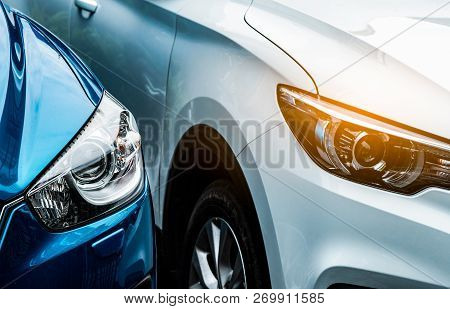 poster of Close Up Headlamp Light Of Blue And White Suv Car. Blue Car Parked Beside White Car. Automotive Indu