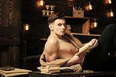 Sexy Student Concept. Man With Muscular Torso, Six Packs, Lay Near Bookshelves, Dark Background. Sma poster