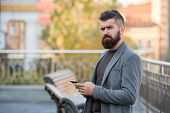Stay In Touch. Man Bearded Serious Businessman Hold Smartphone Urban Background. Hipster Smartphone  poster