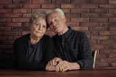 Poor Elderly Couple Sitting And Holding Hands At Table poster