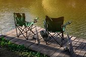 Folding Chairs, Tackle Box And Rods For Fishing On Wooden Pier At Riverside. Recreational Activity poster