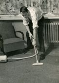 Vintage photo of young man vacuuming (circa 1960)