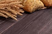 Bread Background On Black Pine Boards With Wheat, A Long Loaf And A Seed Roll. Aromatic Crisp Bread poster
