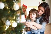Mother And Son Decorating Christmas Tree. Happy Family Play And Decorating Fir Tree For Christmas poster