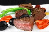 meat savory : grilled beef fillet mignon on white plate with tomatoes apples and pepper over black w