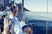 stock photo of life-boat  - sailing man reading tablet computer on boat with modern technology and carefree retired senior successful lifestyle - JPG