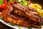 stock photo of ribs  - Tasty grilled ribs with vegetables  - JPG