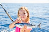 stock photo of troll  - Blond kid girl fishing tuna little tunny happy with trolling catch on boat deck - JPG