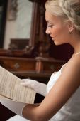 Portrait Of Beautiful Young Woman Reading Vintage Sheet Music