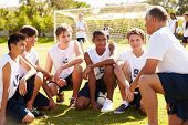 stock photo of football pitch  - Coach Giving Team Talk To Male High School Soccer Team - JPG
