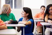 foto of 13 year old  - Teacher Helping Female High School Student In Classroom - JPG