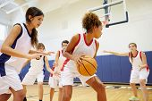 stock photo of indoor games  - Female High School Basketball Team Playing Game - JPG