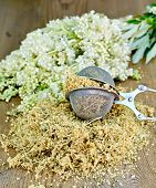 stock photo of meadowsweet  - Metal sieve with dried flowers of meadowsweet a bouquet of fresh flowers of meadowsweet on a wooden boards background - JPG