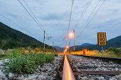 picture of railroad-sign  - Railroad tracks running towards a junction and red sign lights indicating direction - JPG