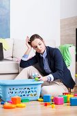 stock photo of superwoman  - Tired woman cleaning up room from kids toys - JPG
