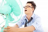 picture of heatwave  - business man suffering a hot summer heat with fans - JPG