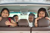 stock photo of goodbye  - Happy Indian family sitting in car smiling - JPG