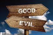 foto of evil  - Good Or Evil concept road sign with blue sky background - JPG