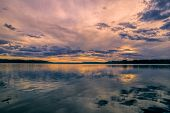 image of windswept  - Breathtaking view of sunset behind windswept sky reflected in a lake - JPG