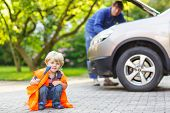 image of breakdown  - Funny child in orange safety vest during his father repairing family car on background - JPG